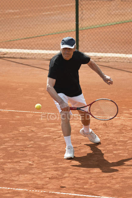 Active senior man playing tennis with racket. — Stock Photo