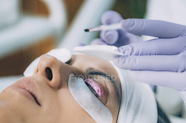 Cosmetologist putting pink paint on patient eyelashes during lash lifting and laminating procedure. — стоковое фото