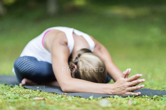 Woman doing yoga and practicing seated forward bend on mat in park. — Stock Photo