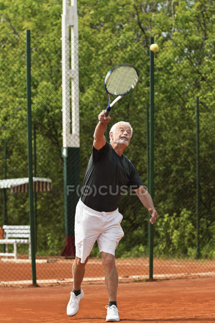 Active senior tennis player serving ball on court. — Stock Photo