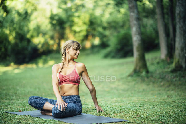 Young woman doing yoga and twisting from lotus position on mat in park. — Stock Photo