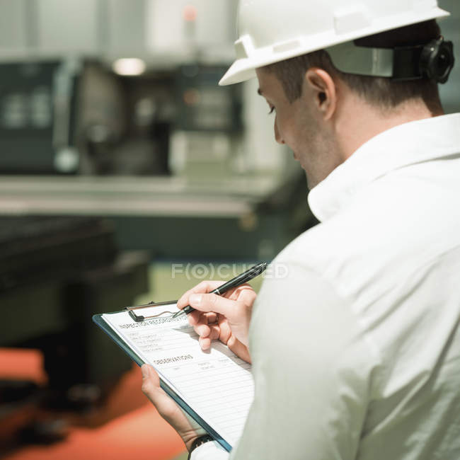 Engineer working in factory. Holding check-list and supervising. — Stock Photo
