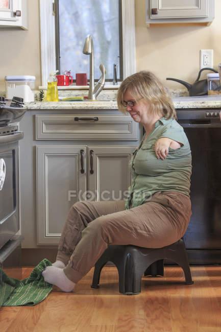 Donna con sindrome di TAR raccogliendo asciugamano da cucina con i piedi . — Foto stock