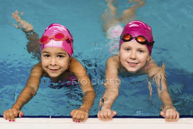 Маленькі дівчата, що практикують у воді басейн. — стокове фото