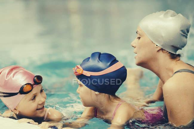 Istruttore femminile avendo con bambini lezione di nuoto in piscina. — Foto stock