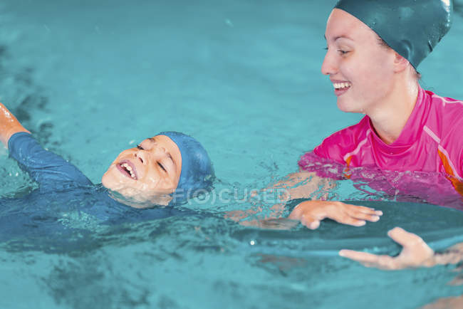 Boy in swimming class with instructor in public pool. — Stock Photo