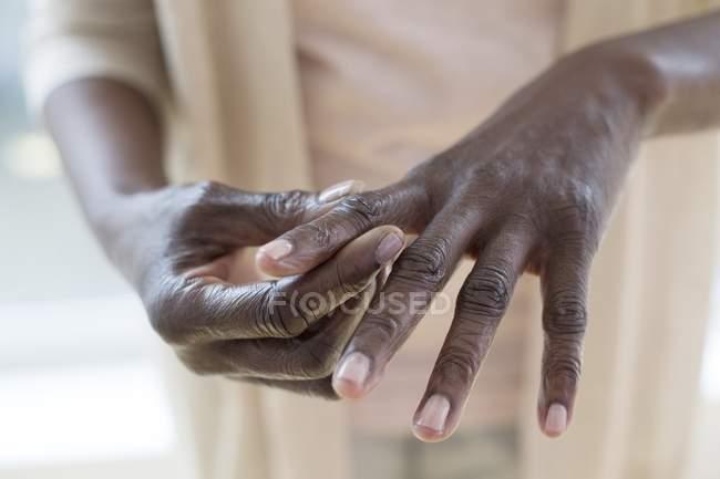 Primer plano de la mujer madura sosteniendo el dedo con dolor . - foto de stock