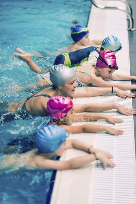 Group of children in swimming class with instructor practicing kicking. — Stock Photo
