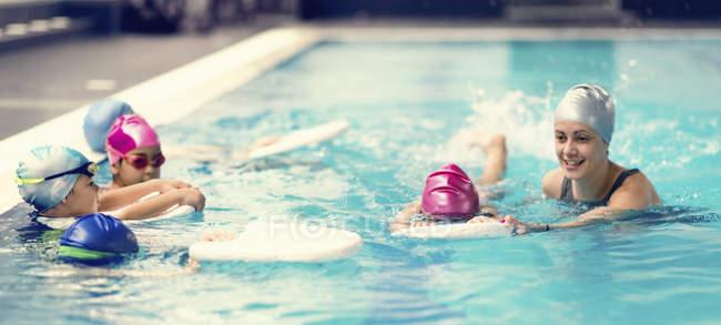 Gruppo di bambini in età prescolare durante il nuoto in acqua di piscina con istruttore. — Foto stock