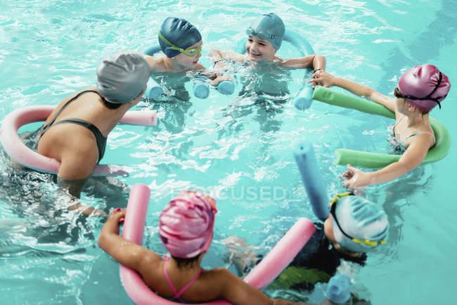 Instructeur avec groupe d'enfants s'amusant à l'école de natation . — Photo de stock