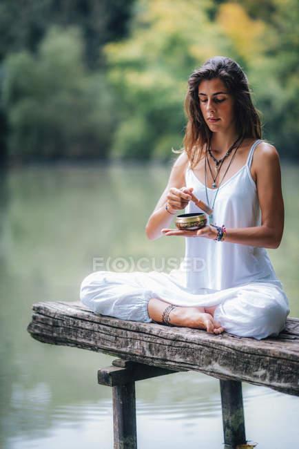 Giovane donna che tiene una ciotola tibetana sul molo di legno vicino all'acqua del lago . — Foto stock