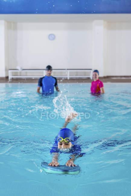 Ragazzo che ha lezione di nuoto con istruttori in piscina. — Foto stock