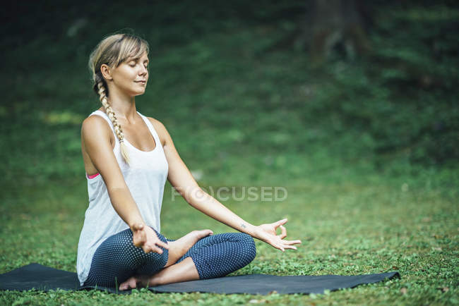 Young woman doing yoga and sitting in half lotus position on mat in park. — Stock Photo