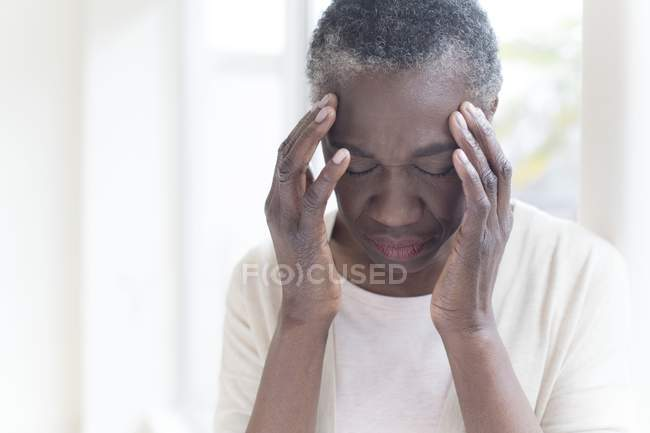 Mature woman touching head in pain with hands. — Stock Photo