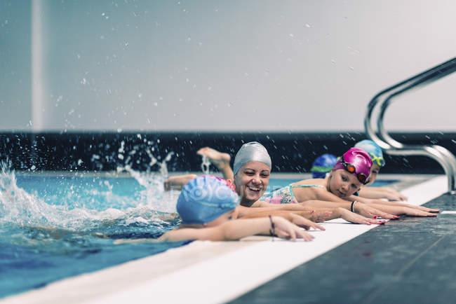 Istruttore femminile con bambini in età prescolare durante il nuoto in piscina. — Foto stock