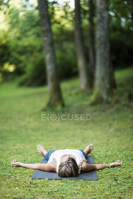 Woman doing yoga on mat in park, meditating in shavasana position. — Stock Photo