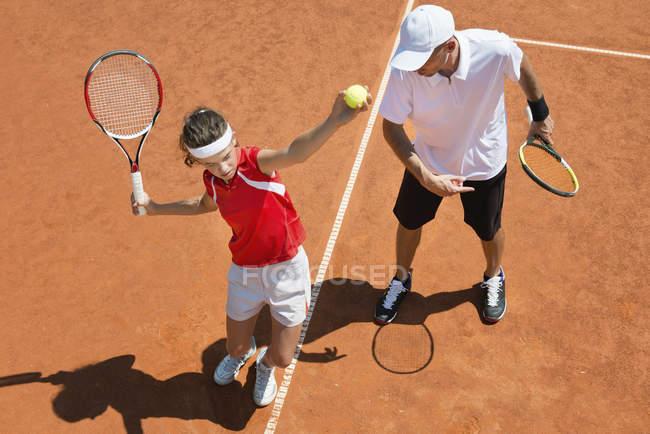 Giocatore di tennis adolescente che pratica il servizio con allenatore di tennis . — Foto stock