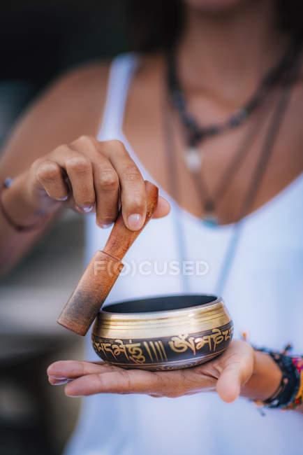 Primo piano di mani femminili che tengono la ciotola tibetana all'aperto . — Foto stock