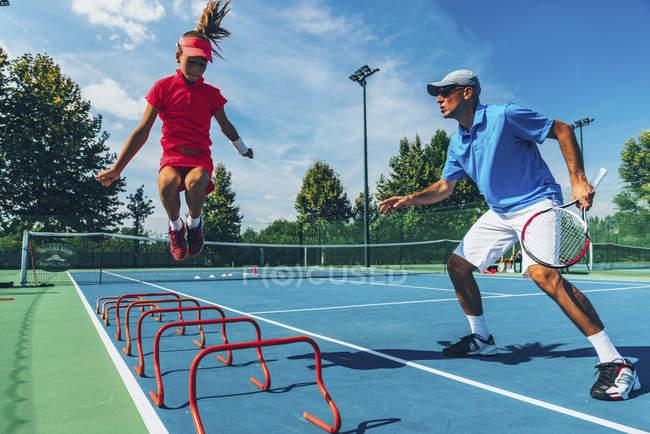 Підлітки тенісист стрибає з чоловічий інструктор в теніс клас. — стокове фото