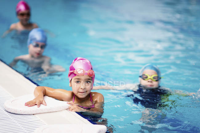 Gruppo di bambini in età prescolare durante il nuoto in acqua della piscina. — Foto stock