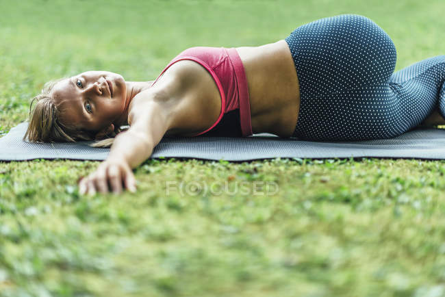 Young woman doing yoga, practicing reclining spinal twist position on mat in park. — Stock Photo