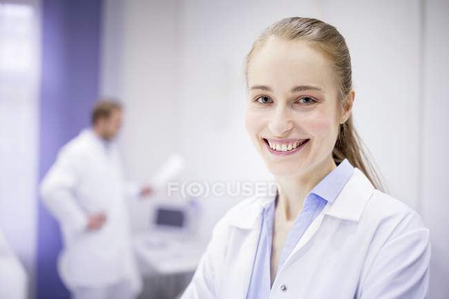 Female doctor smiling in clinic, male doctor in background. — Stock Photo