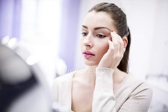Mulher olhando para o rosto no espelho na clínica de cosméticos . — Fotografia de Stock