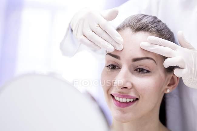 Руки лікаря вивчення молодого жіночого чола. — стокове фото