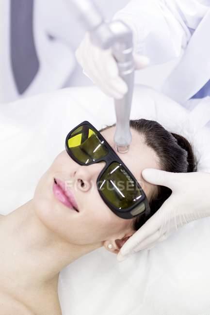 Técnico de belleza usando tratamiento láser en cliente femenino . - foto de stock