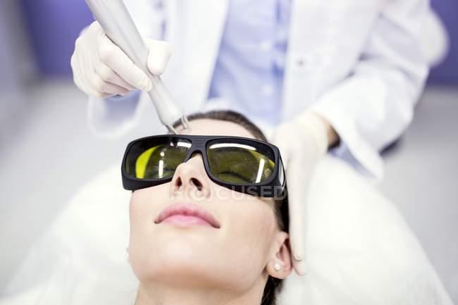Técnico de belleza usando tratamiento láser . - foto de stock
