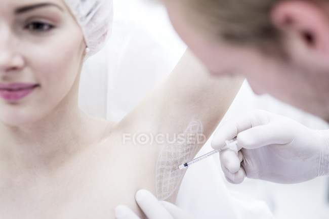 Dermatologist injecting botox in underarm to treating