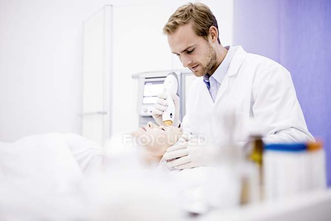 Dermatologist giving thermage treatment to mature woman face to softening wrinkles. — Stock Photo