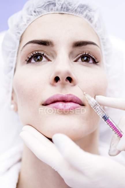 Giovane donna che inietta botox iniettabile sul viso, primo piano . — Foto stock