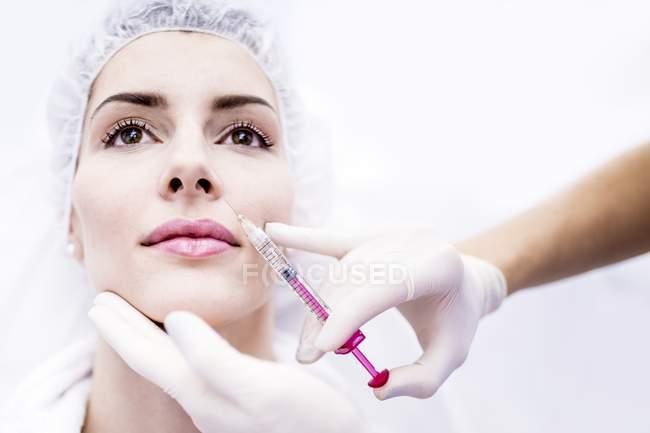 Молода жінка ін'єкційні Ботокс ін'єкції на обличчі, Крупний план. — стокове фото