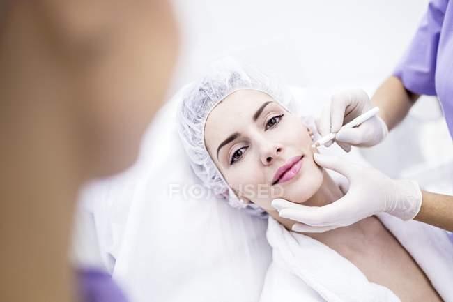 Dermatologe zeichnet Flecken auf Frauengesicht für Thread-Lifting, Nahaufnahme. — Stockfoto