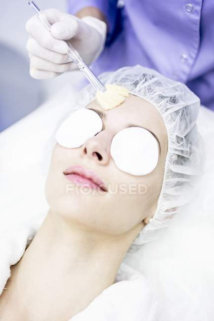 Dermatologist cleaning face after microdermabrasion treatment in clinic, close-up. — Stock Photo