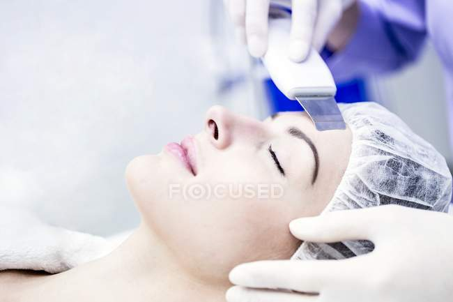 Mulher nova que recebe o tratamento facial do microdermabrasion na clínica, close-up. — Fotografia de Stock