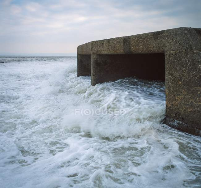 Cooling water outfall into sea from power station, UK. — Stock Photo