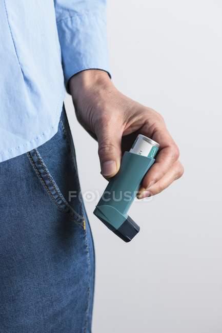 Primo piano dell'inalatore per l'asma a mano maschile . — Foto stock