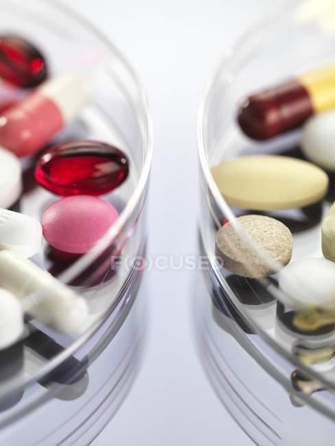 Variedade farmacêutica de cápsulas de medicamentos em placas de Petri . — Fotografia de Stock