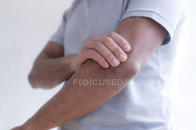 Uomo che tocca gomito nel dolore, primo piano . — Foto stock