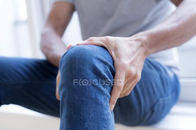 Uomo che tiene il ginocchio dolorante, primo piano . — Foto stock