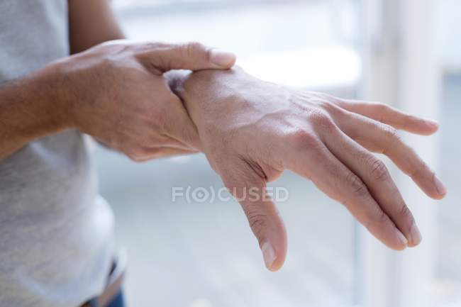 Man touching wrist in pain, close-up. — Stock Photo