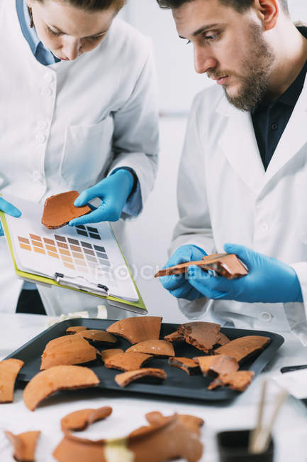 Archaeologists comparing pottery colors with color chart scheme in laboratory. — Stock Photo