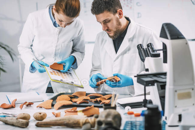 Young archaeologists comparing pottery colors with color chart scheme in laboratory. — Stock Photo