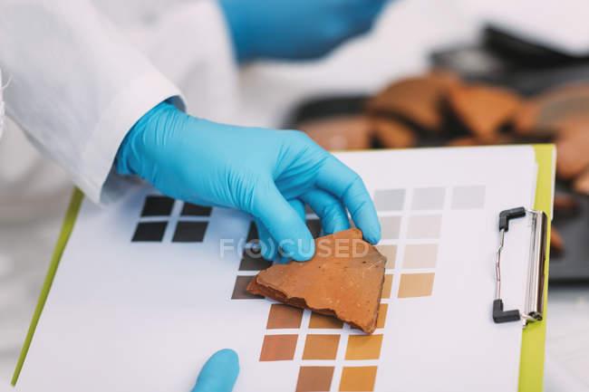Руки археолога порівнюють кольори кераміки з схемою кольорових діаграм у лабораторії.. — стокове фото