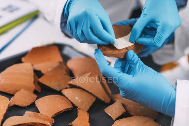 Mani di archeologi che ricostruiscono ceramiche rotte in laboratorio . — Foto stock