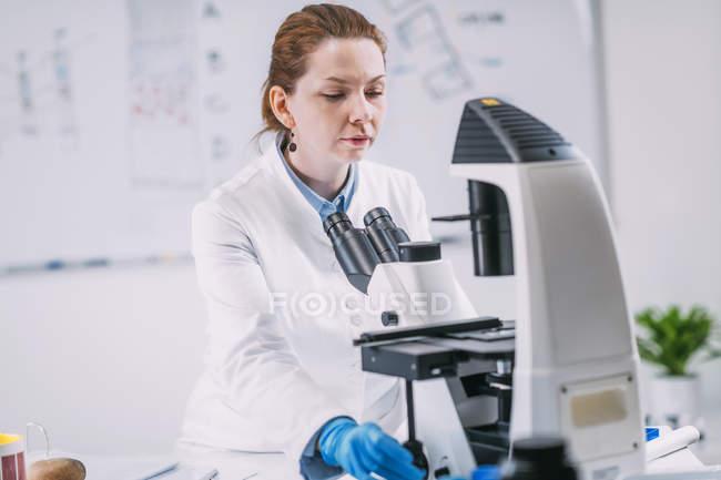 Retrato de una joven arqueóloga usando microscopio en laboratorio . - foto de stock