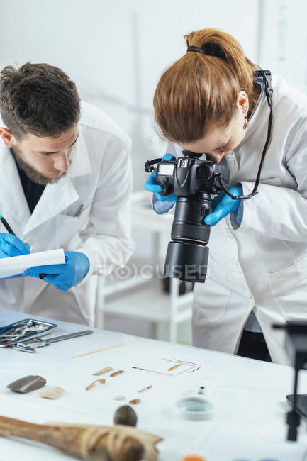 Young archaeology researchers documenting lithics with camera in laboratory. — Stock Photo