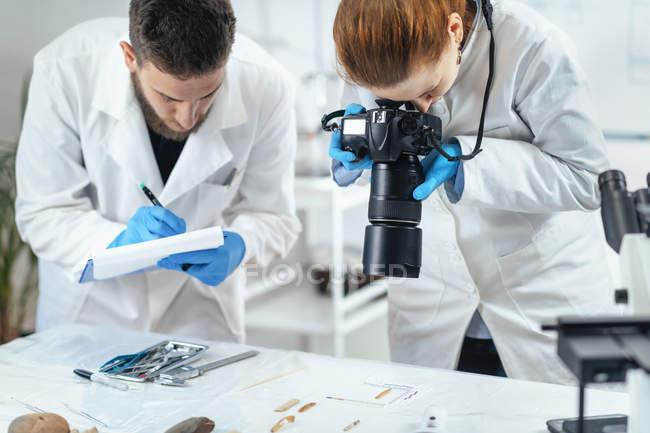 Jóvenes investigadores de arqueología documentando la lítica con cámara en laboratorio . - foto de stock